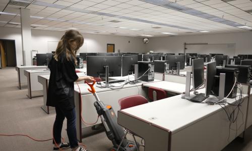Janitor vacuuming carpet floors in computer lab