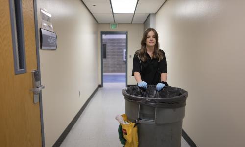 Janitor walking down hallway with trashcan