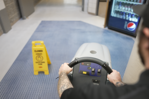 Janitor operating commercial floor cleaning machine