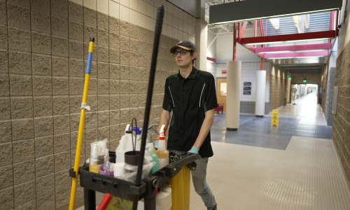 Janitor walking in a hallway with cleaning cart