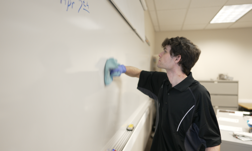 Janitor cleaning whiteboard in classroom