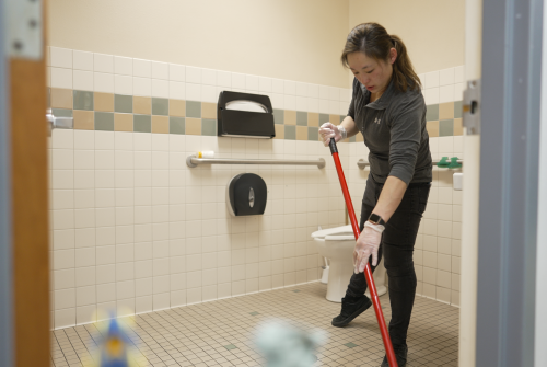 Janitor cleaning floors of bathroom with mop